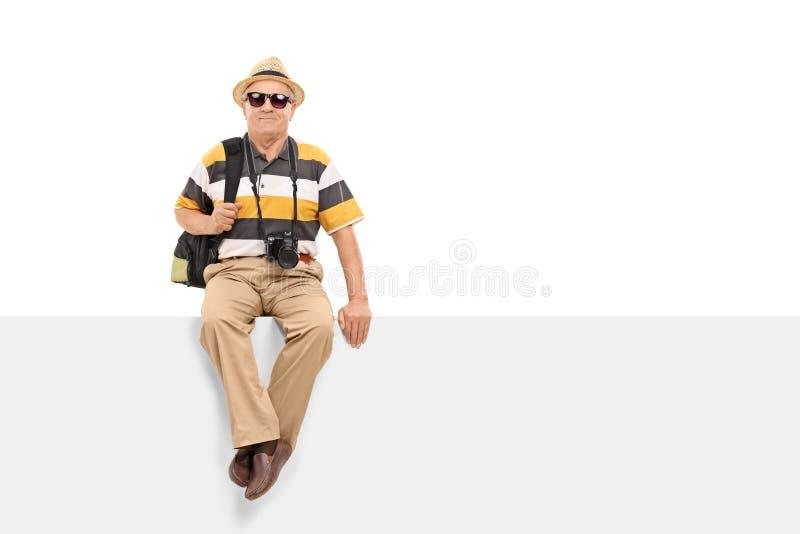 Sentada turística madura en una cartelera en blanco foto de archivo libre de regalías