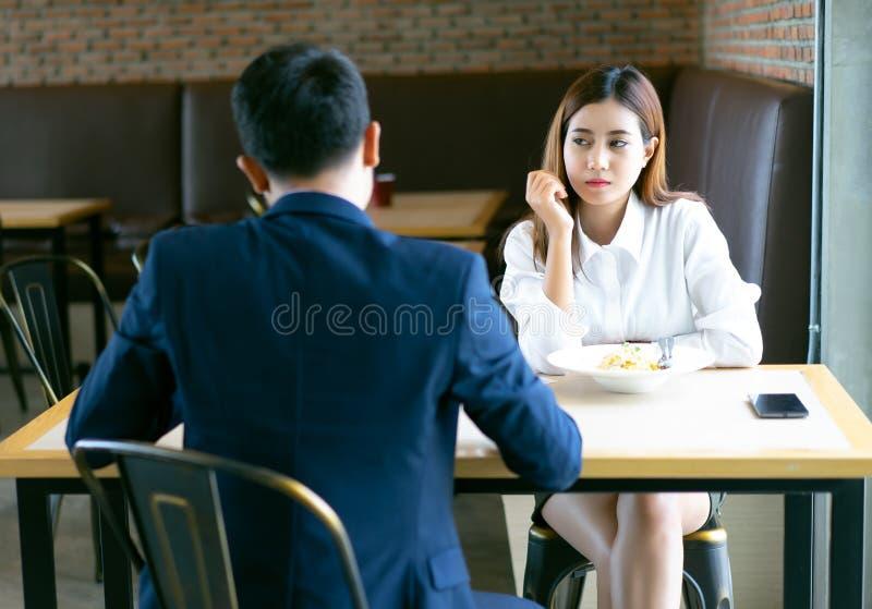 Sentada y almuerzo asiáticos agujereados cansados de la muchacha con su novio en un café y la mirada lejos Los pares emocionales  foto de archivo