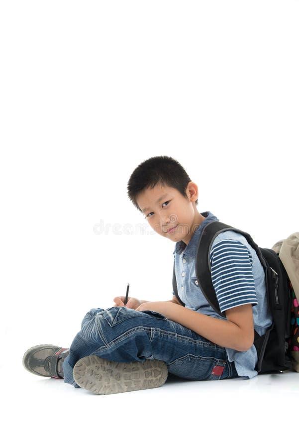 Sentada y escritura asiáticas del muchacho del estudiante algo fotografía de archivo