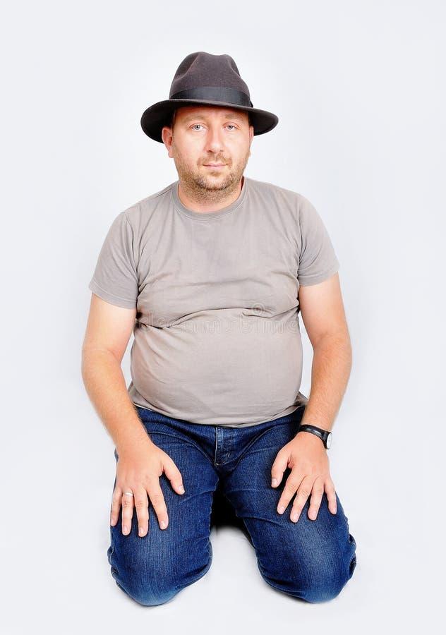 Sentada y explotación agrícola jovenes del varón un sombrero en la pista imagen de archivo libre de regalías