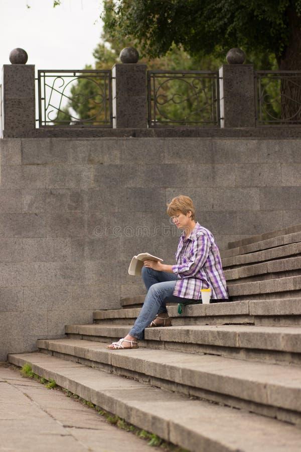 Sentada y lectura positivas de la mujer un libro imágenes de archivo libres de regalías