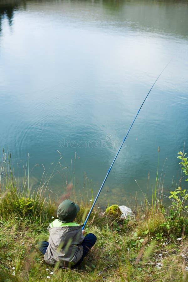 Sentada y pesca jovenes del muchacho imagen de archivo
