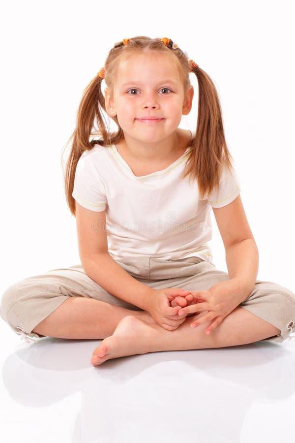 Sentada y sonrisa hermosas de la niña foto de archivo libre de regalías