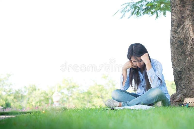 Sentada y trabajo serios de la empresaria difícilmente en campos de una hierba verde fotos de archivo libres de regalías