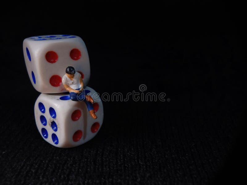 Sentado Mini Figura Homem de Brinquedo segurando smartphone em um disco de plástico branco, Ilustração para Gamble on-line foto de stock royalty free