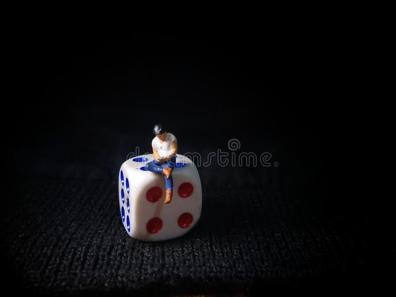 Sentado Mini Figura Homem de Brinquedo segurando smartphone em um disco de plástico branco, Ilustração para Gamble on-line fotos de stock