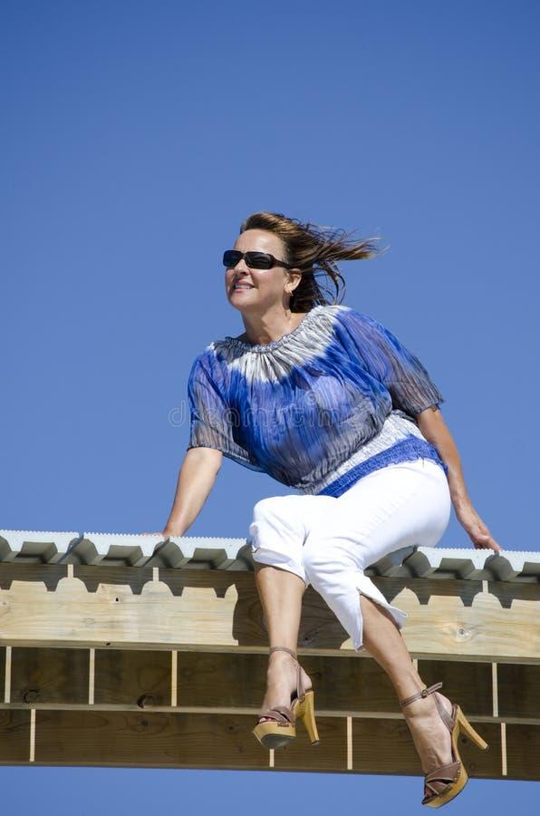 Sentar relajado mujer y disfrutar de la sol fotos de archivo