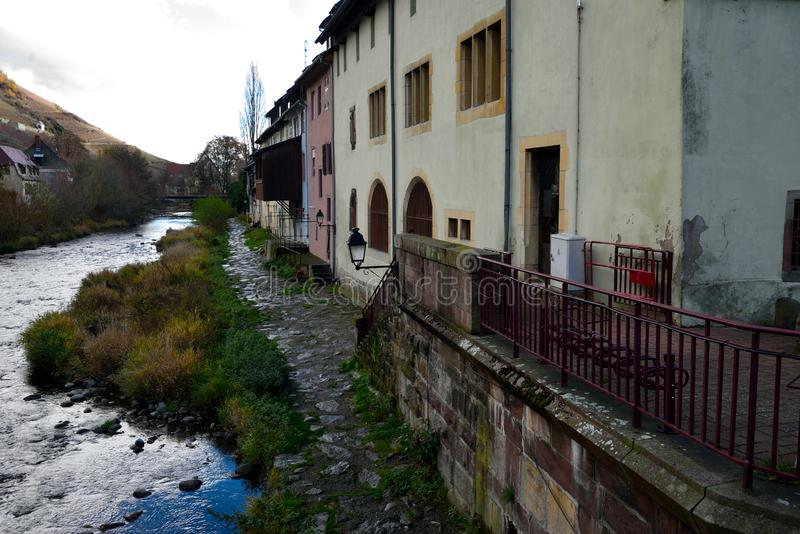 Sentier de la Berge. Narrow trail along the River Thur in the town of Thann. Thann is situated at the foot of the Vosges mountains, at the mouth of the valley stock photography