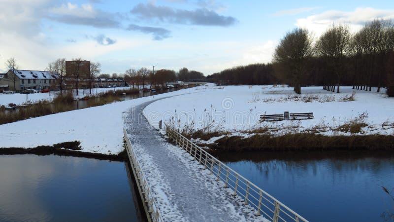Sentier piéton menant au-dessus du canal à Forest Covered en neige et glace images stock