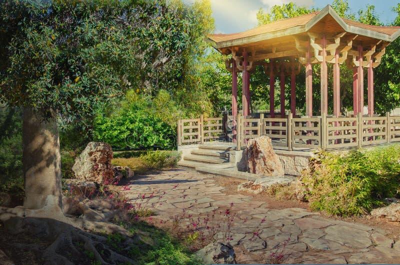 Sentiero per pedoni di pietra che conduce al gazebo di legno asiatico fotografie stock