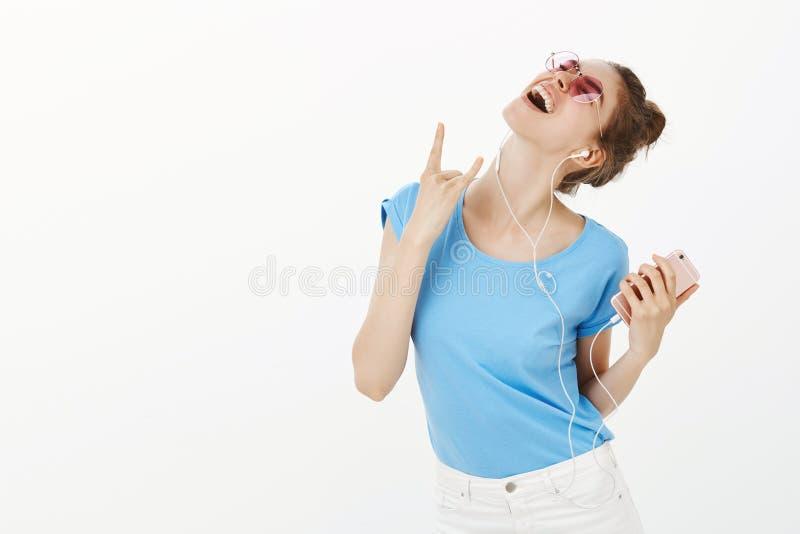 Sentiment de fille comme sur le concert vivant tandis que musique de écoute dans des écouteurs tous neufs Femme insouciante entho images stock