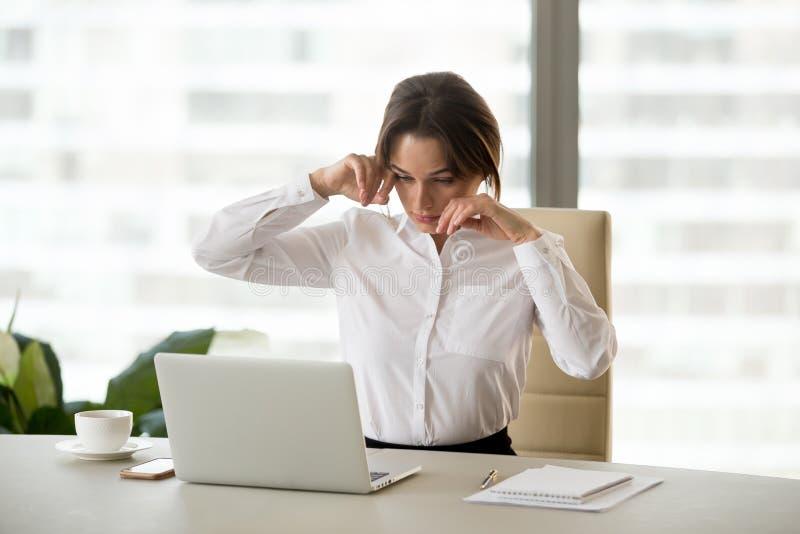 Sentiment fatigué de femme d'affaires fatigué de l'ordinateur touchant l'IR sec images stock