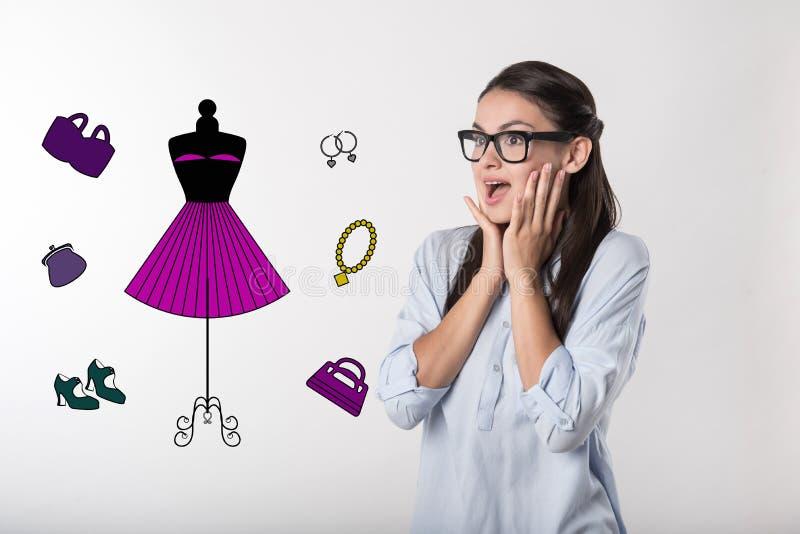 Sentiment modèle enthousiaste appliqué tout en voyant sa nouvelle robe photo libre de droits