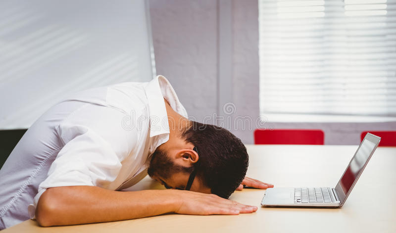 Sentiment occasionnel d'homme d'affaires épuisé à son bureau photos stock