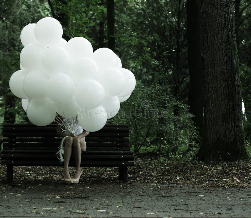 Sentimentalitet. Nostalgi. Ensam kvinna med luftballonger som sitter på bänk i parkera arkivfoto