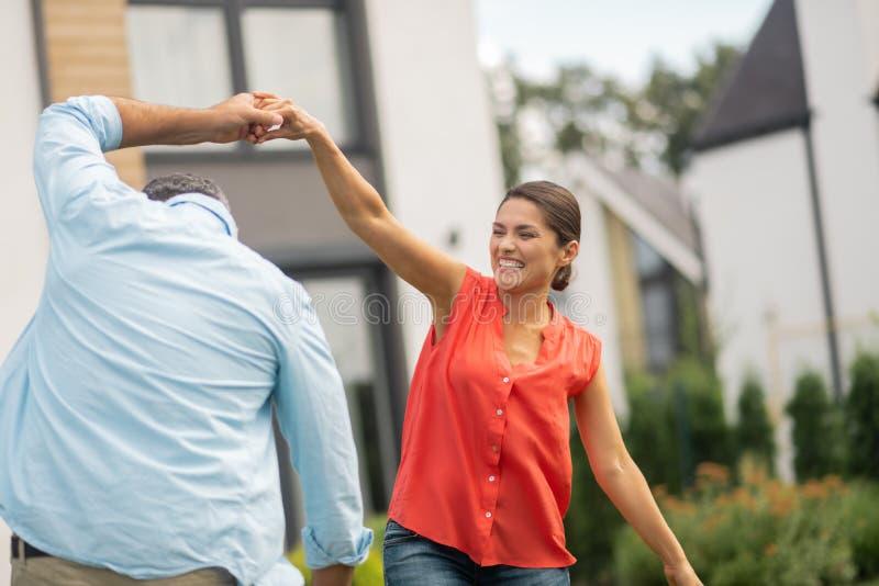 Sentimento alegre dos pares que surpreende ao dançar perto da casa fotos de stock royalty free