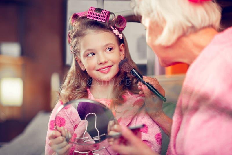 Sentimento bonito de olhos escuros da menina excitado fazendo a composição com avó imagem de stock