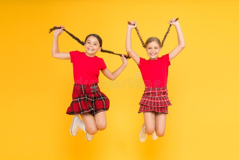 Sentimento brincalh?o Olhar da beleza crianças felizes na parede amarela Felicidade da inf?ncia farda da escola na moda Salto eng fotografia de stock