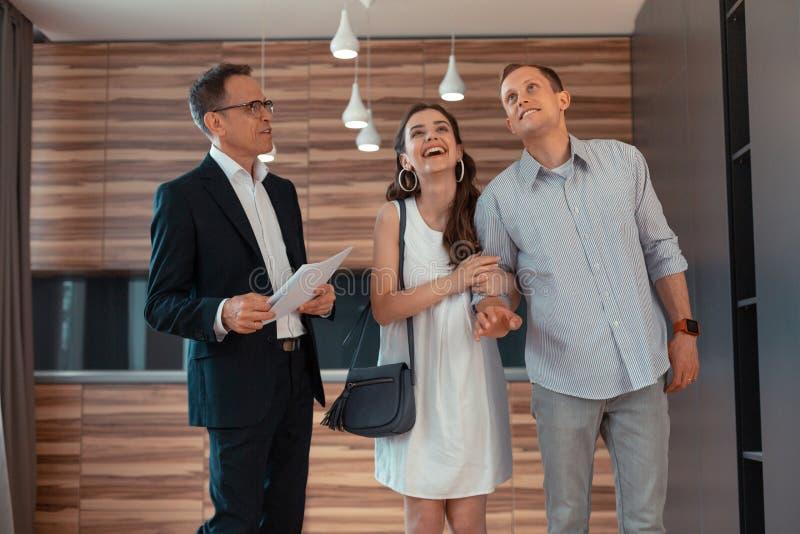 Sentimento da esposa que surpreende ao comprar o apartamento novo com marido foto de stock