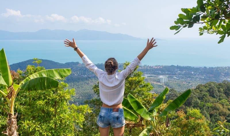 Sentimento da liberdade Menina que aumenta suas mãos acima no ponto de vista tropical Vista excitante fotos de stock royalty free