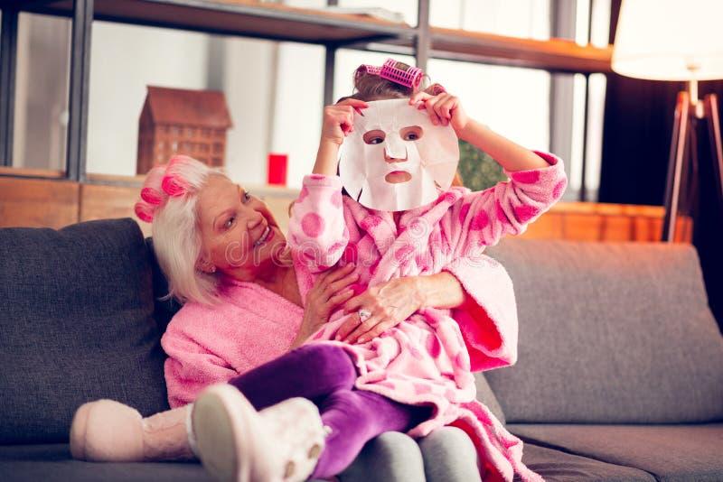 Sentimento da menina curioso ao tentar a máscara da folha no assento perto da avó fotos de stock royalty free