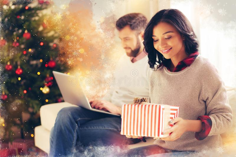 Sentimento de cabelo escuro bonito da esposa excitado antes de abrir a caixa de presente do Natal imagem de stock