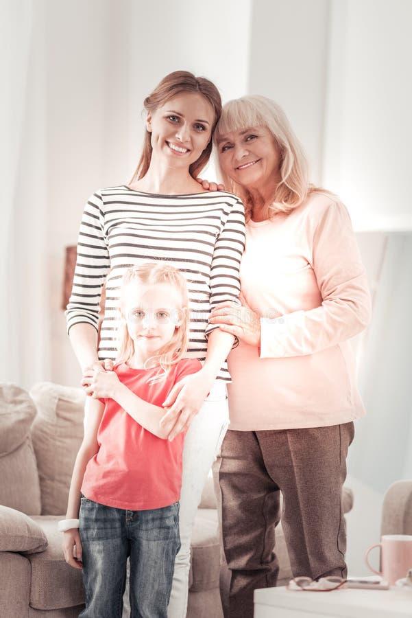 Sentimento de cabelos compridos louro doce da menina relaxado com sua família fotografia de stock royalty free