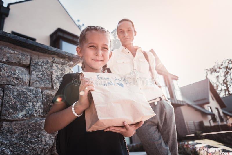 Sentimento de irradiação da menina feliz após ter recebido o presente de seu pai foto de stock royalty free