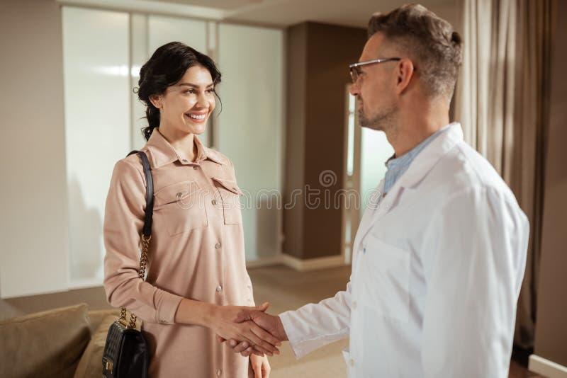 Sentimento de olhos escuros da mulher excitado ao encontrar o cirurgião de cosméticos imagem de stock royalty free