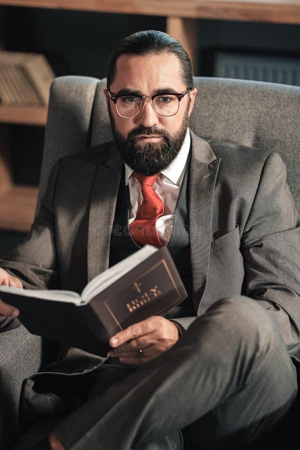Sentimento do homem de negócios pensativo ao ler a Bíblia imagem de stock