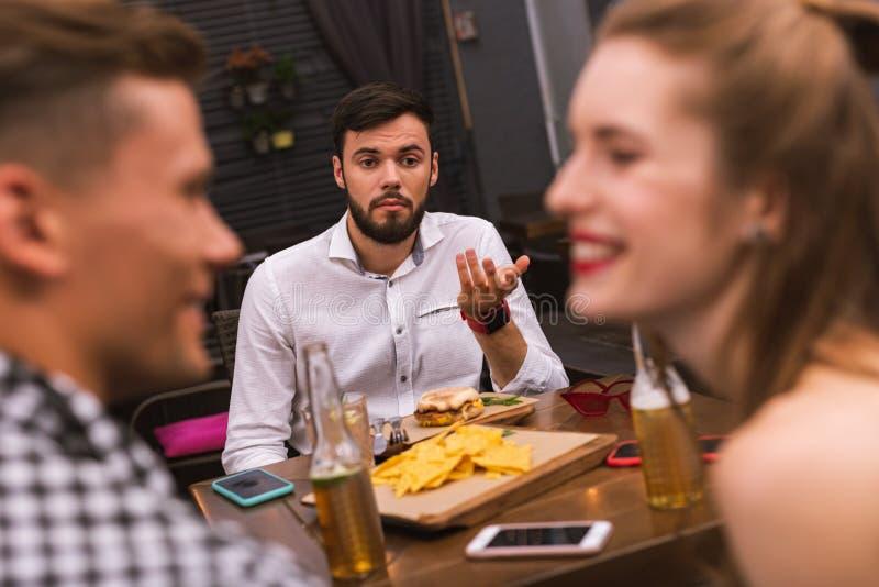 Sentimento do homem novo virado ao ver seus amigos flertar imagem de stock royalty free
