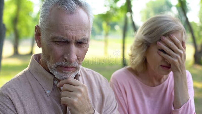 Sentimento do homem superior triste e culpado, assento de grito da esposa distante, divórcio dos pares imagens de stock