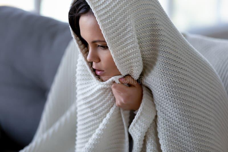 Sentimento doente da mulher frio tendo os sintomas da gripe cobertos com a cobertura fotografia de stock