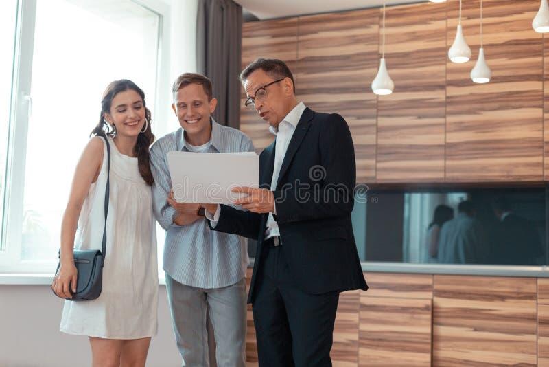 Sentimento dos pares excitado ao falar com o mediador imobiliário foto de stock royalty free
