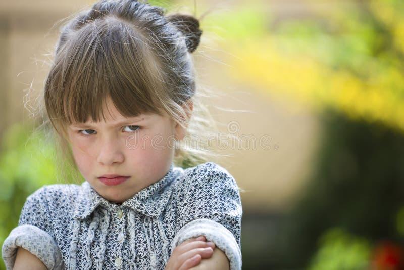 Sentimento exterior da menina temperamental engraçada bonita da jovem criança irritado e insatisfeito no fundo borrado do verde d imagens de stock
