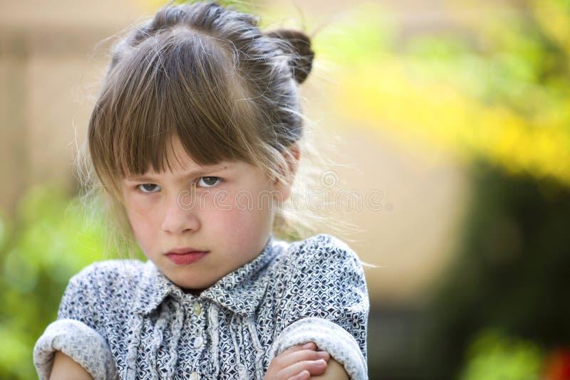 Sentimento exterior da menina temperamental engra?ada bonita da jovem crian?a irritado e insatisfeito no fundo borrado do verde d foto de stock