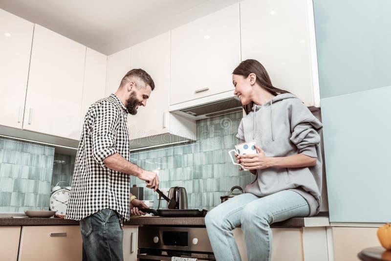 Sentimento farpado do homem alegre ao fazer o jantar para a esposa imagens de stock