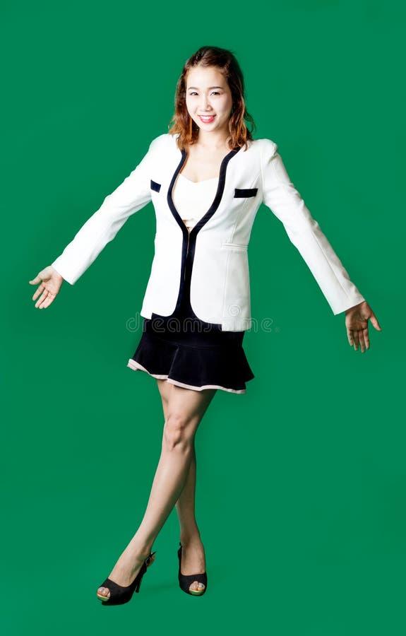 Sentimento feliz do braço aberto da mulher de funcionamento do oficial da senhora em seixos verdes imagem de stock
