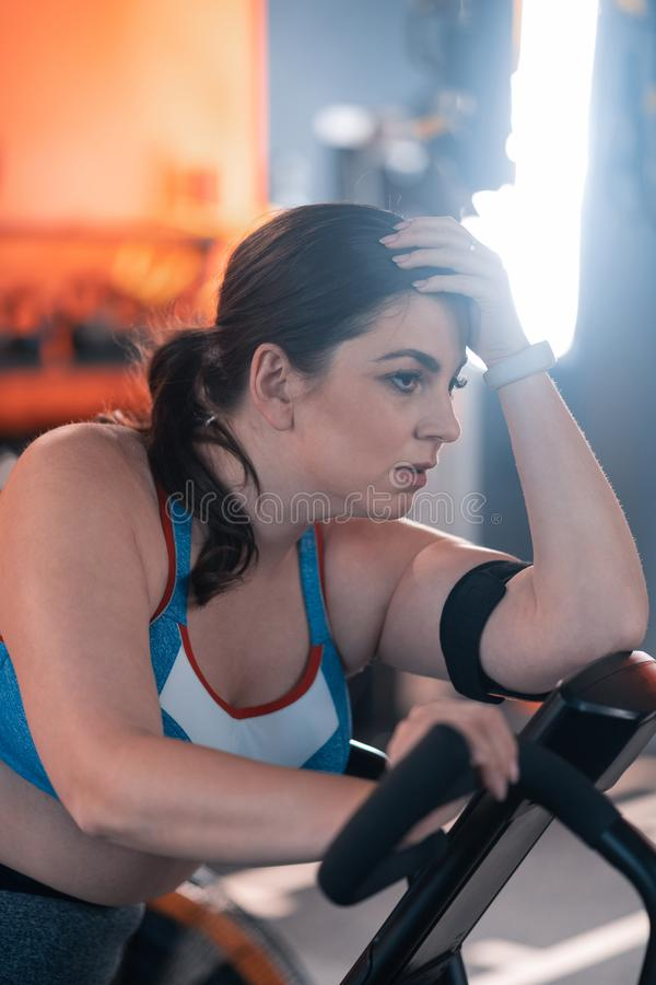 Sentimento gordo da mulher esgotado e cansado após a ciclagem no gym imagens de stock