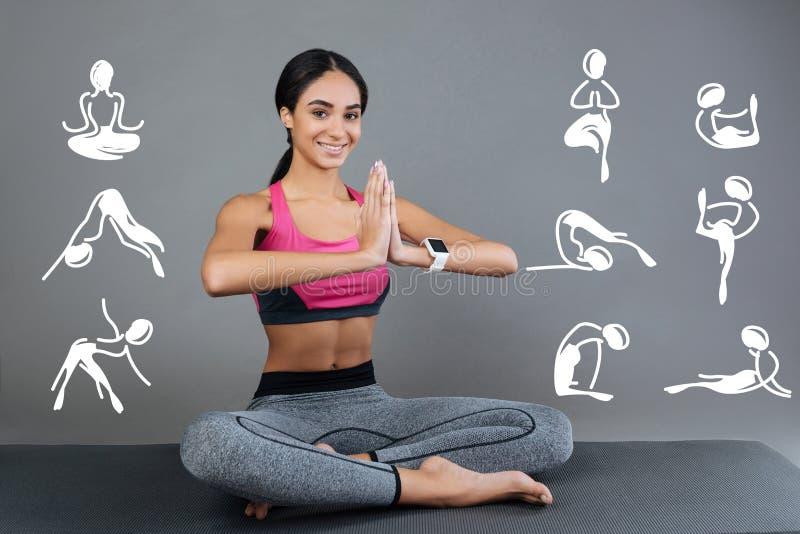 Sentimento positivo da jovem mulher feliz e que sorri ao praticar a ioga fotografia de stock