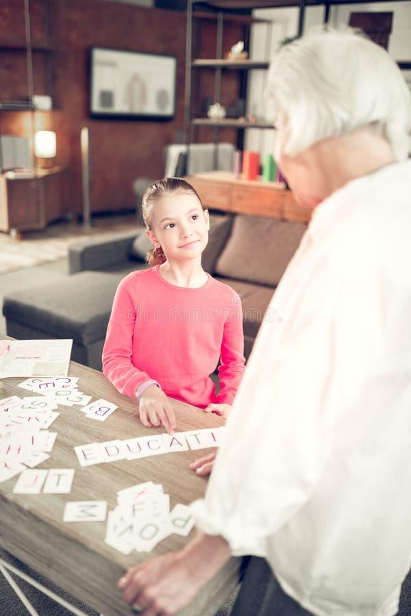Sentimento pré-escolar de olhos escuros da menina envolvido na aprendizagem com a avó fotos de stock