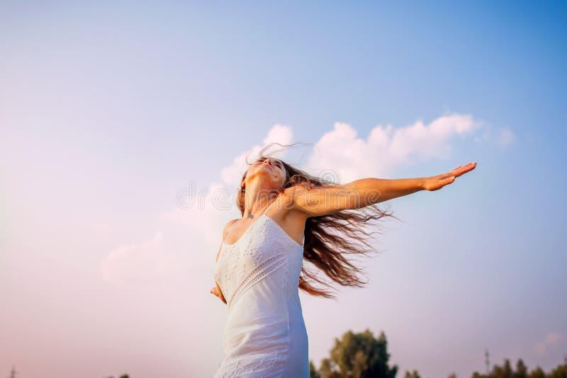 Sentiresi libero della giovane donna e armi d'innalzamento felici e che fila intorno aria aperta al tramonto fotografia stock