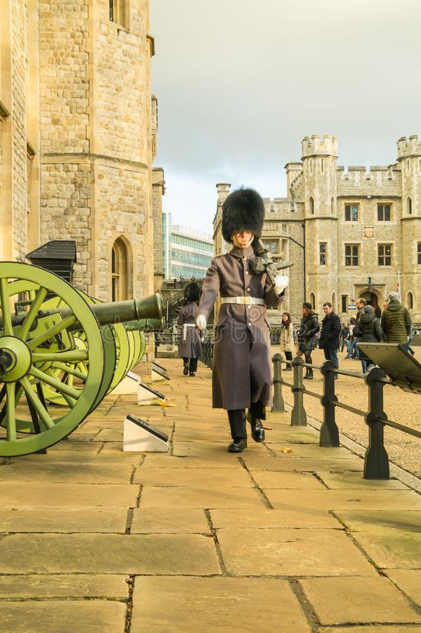 Sentry in uniform marching at the Tower of London, carrying gun. Guard in uniform marching at the Tower of London, carrying gun with bayonet, in front of stock photos