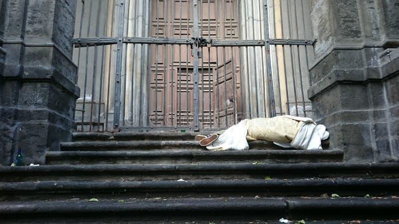 Senzatetto ruvido addormentato sulle scale della costruzione davanti al portone fotografia stock