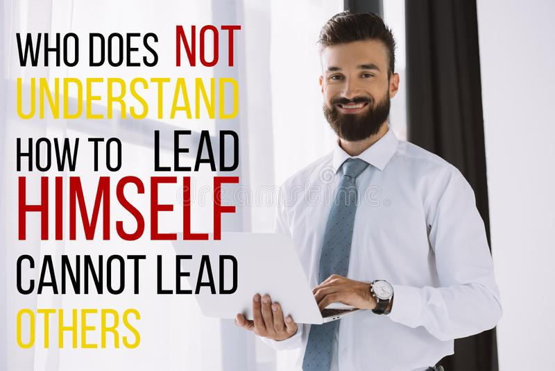 bearded smiling businessman using laptop near window with who does not understand how to lead himself cannot stock image