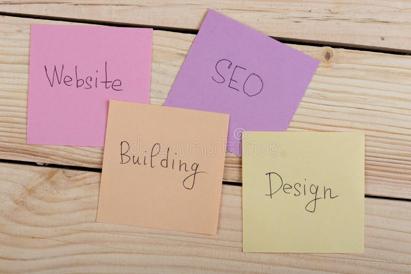 Seo concept - colorful sticky notes with words design, website, seo, building. On wooden background royalty free stock photo