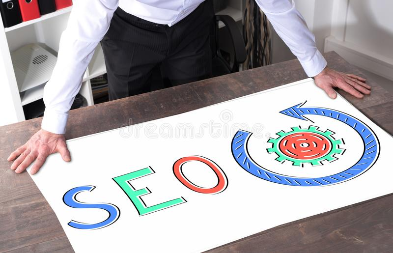 Seo concept on a desk. Man watching a seo concept placed on a desk royalty free stock photography