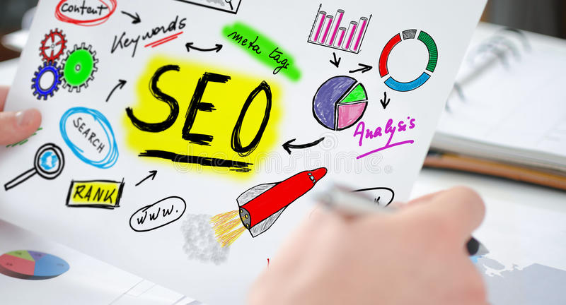 Seo concept on a paper. Hands holding a paper showing a seo concept royalty free stock photos