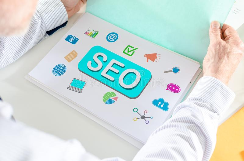 Seo concept on a paper. Man holding a file with seo concept stock images