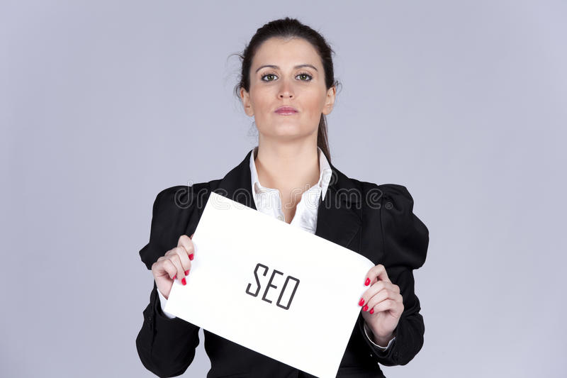 SEO expert. Businesswoman holding a paper with the word SEO stock photo